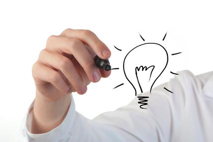 Woman's hand drawing a light globe with a felt pen